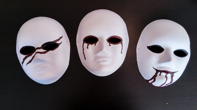Three identical white masks, slightly altered by paint. One has red tears running down it's cheeks. One has blood dripping from it's mouth. One has two long, red scars across it's face.